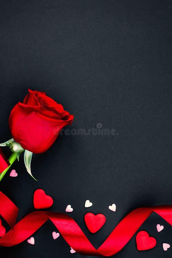 Fondo hermoso de día de San Valentín con las rosas rojas y los corazones en fondo negro Endecha plana, espacio de la copia fotografía de archivo