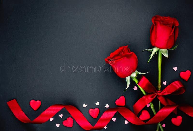 Fondo hermoso de día de San Valentín con las rosas rojas y los corazones en fondo negro Endecha plana, espacio de la copia imagen de archivo
