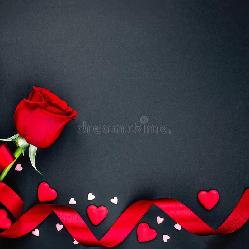 Fondo hermoso de día de San Valentín con las rosas rojas y los corazones en fondo negro Endecha plana, espacio de la copia imagen de archivo libre de regalías