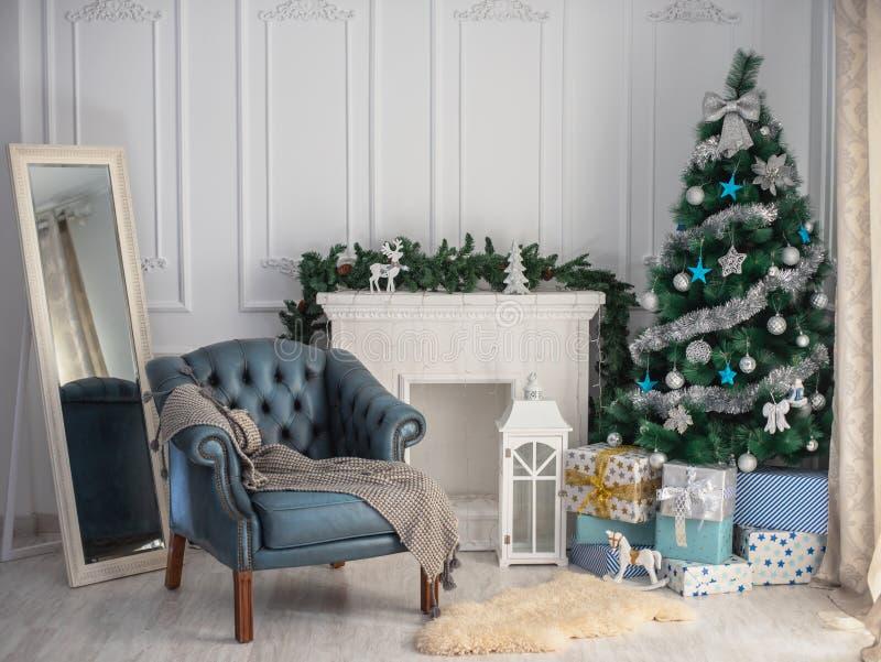 Fondo hermoso de la Navidad con el árbol de navidad y la silla azul foto de archivo