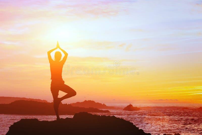 Fondo hermoso de la yoga, silueta de la mujer en la playa en la puesta del sol, mindfulness fotografía de archivo libre de regalías