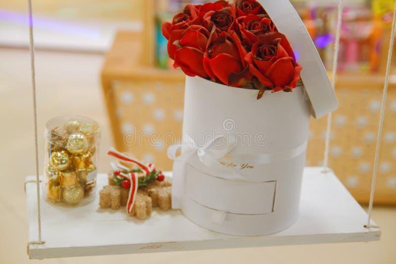 Fondo hermoso para el día del ` s de la tarjeta del día de San Valentín Rosas rojas en una cesta y chocolates en un tablero de ma imagenes de archivo
