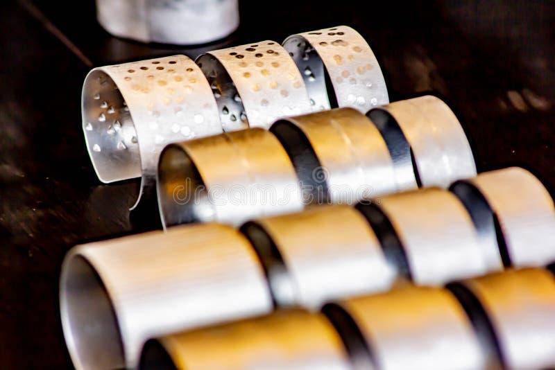 Fondo, imagen del primer de una fila de las pulseras de la chapa handcrafted en el sitio, foto tomada en un comercio justo en Tre imagen de archivo libre de regalías
