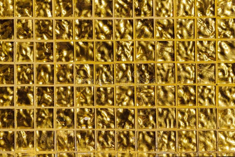 Fondo impresso oro, cellule quadrate Piccole mattonelle dorate sulla parete immagini stock