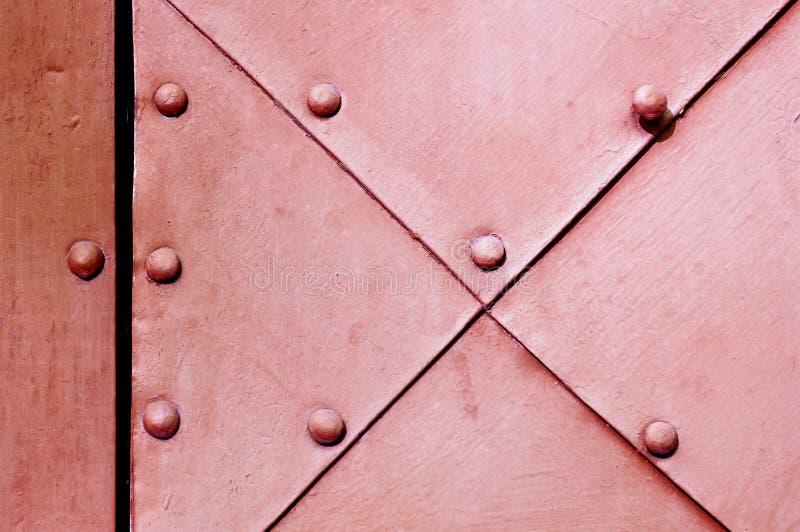 Fondo industrial - superficie del grunge de la puerta rosada oscura del metal viejo con los remaches imagenes de archivo