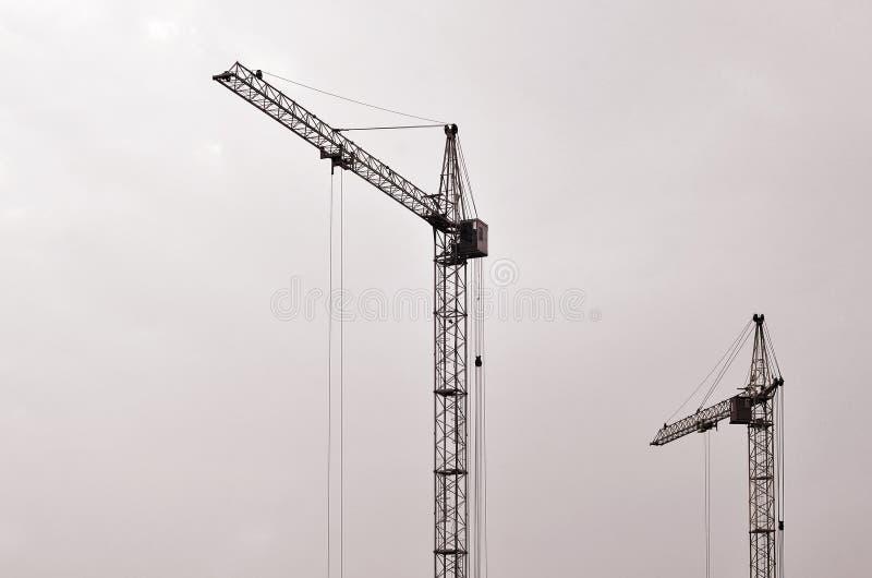 Fondo industriale astratto con le gru a torre della costruzione sopra chiaro cielo blu Mattoni che si situano all'aperto Costruzi fotografie stock libere da diritti