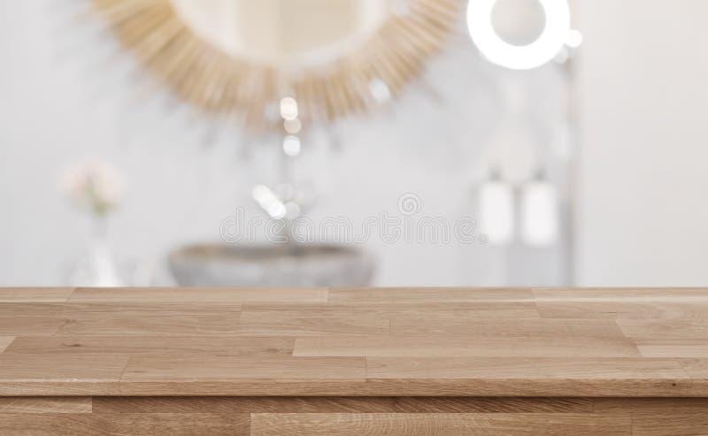 Fondo interior borroso del fregadero del cuarto de baño con la tabla de madera en frente fotografía de archivo