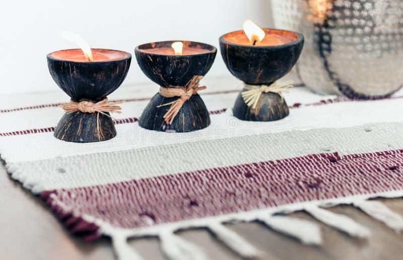 Fondo interior casero acogedor de la decoración, velas ardientes en cáscara del coco en una manta multicolora imagenes de archivo