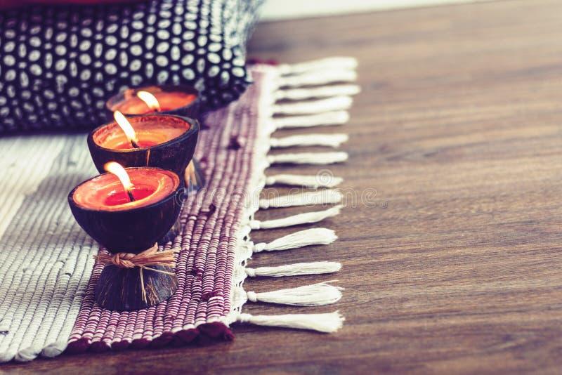 Fondo interior casero acogedor de la decoración, velas ardientes en cáscara del coco en una manta multicolora fotos de archivo libres de regalías