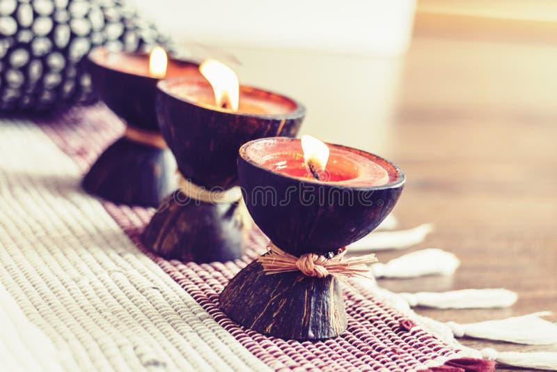 Fondo interior casero acogedor de la decoración, velas ardientes en cáscara del coco en una manta multicolora fotos de archivo