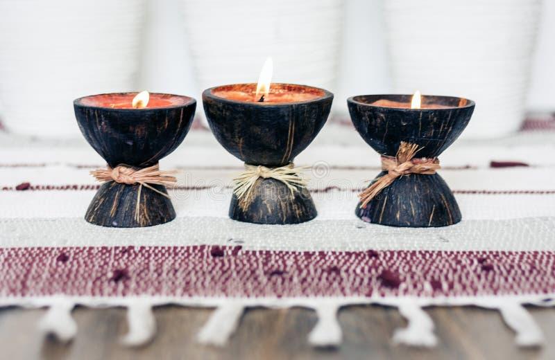 Fondo interior casero acogedor de la decoración, velas ardientes en cáscara del coco en una manta multicolora foto de archivo