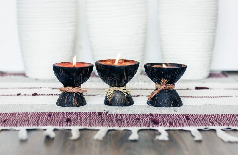 Fondo interior casero acogedor de la decoración, velas ardientes en cáscara del coco en una manta multicolora imágenes de archivo libres de regalías