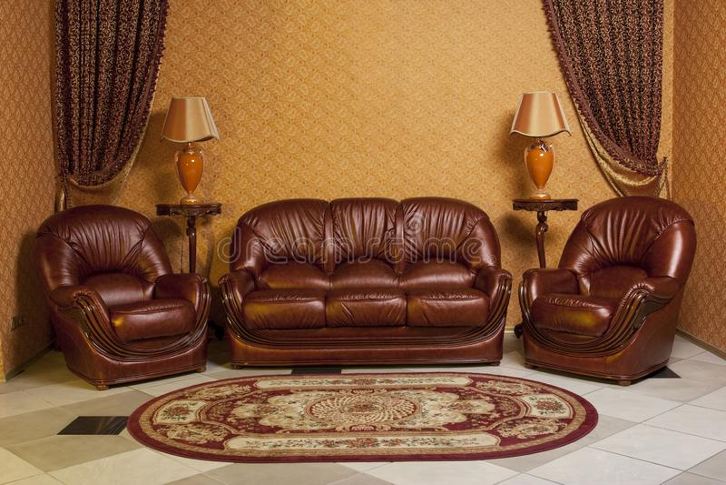 Fondo interior vacío de la sala de estar en colores calientes adornado con muebles de cuero de lujo clásicos imagen de archivo