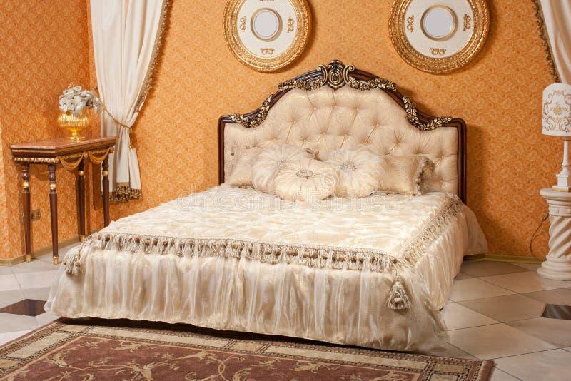 Fondo interno vuoto della camera da letto a colori i colori caldi decorato con mobilia classica fotografia stock libera da diritti