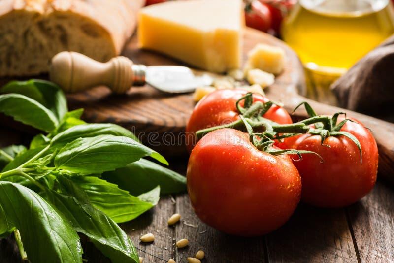 Fondo italiano de la comida con los tomates en vid, albahaca, aceite de oliva, queso parmesano y pan del ciabatta imagen de archivo