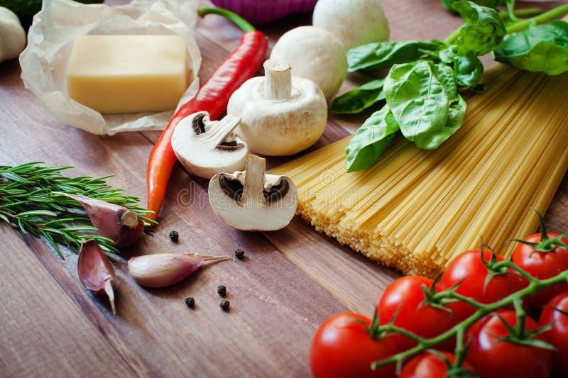 Fondo italiano dell'alimento, con i pomodori della vite, basilico, spaghetti, funghi, parmigiano, aglio, granelli di pepe, rosmar fotografia stock libera da diritti