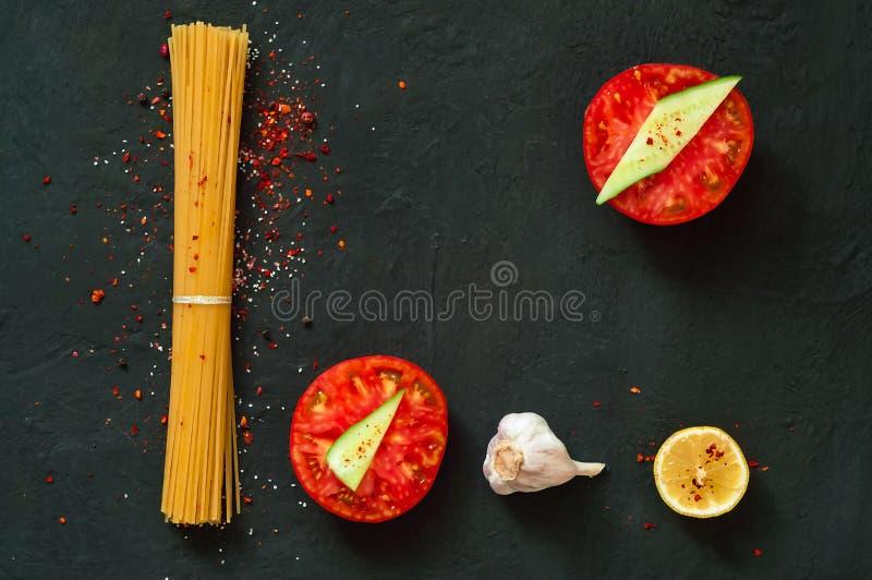 Fondo italiano dell'alimento con i pomodori, gli spaghetti, l'aglio, i granelli di pepe ed il limone Fondo dell'ardesia, spazio d fotografie stock libere da diritti
