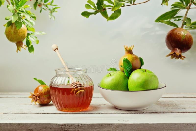 Fondo judío de Rosh Hashana (Año Nuevo) del día de fiesta con el tarro de la miel, las manzanas y el árbol de granada fotos de archivo libres de regalías