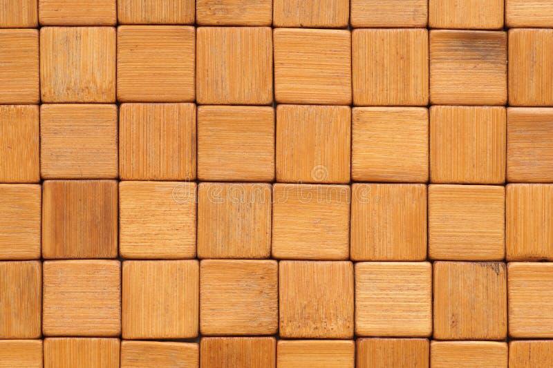 Fondo La stuoia è fatta dei blocchi di legno di bambù quadrati, insabbiati e verniciati immagine stock libera da diritti