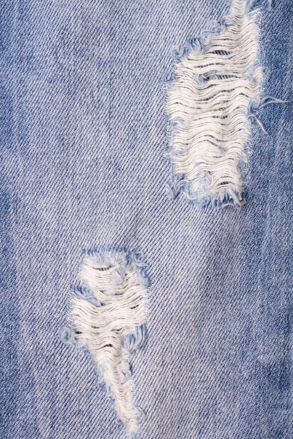 Fondo lacerato distrutto delle blue jeans Fine sui jeans strappati blu fotografia stock