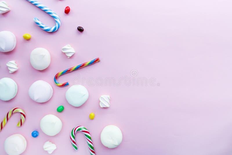 Fondo lindo del partido del feliz cumpleaños: melcochas en el fondo rosado con el espacio en blanco para el texto, visión superio fotos de archivo