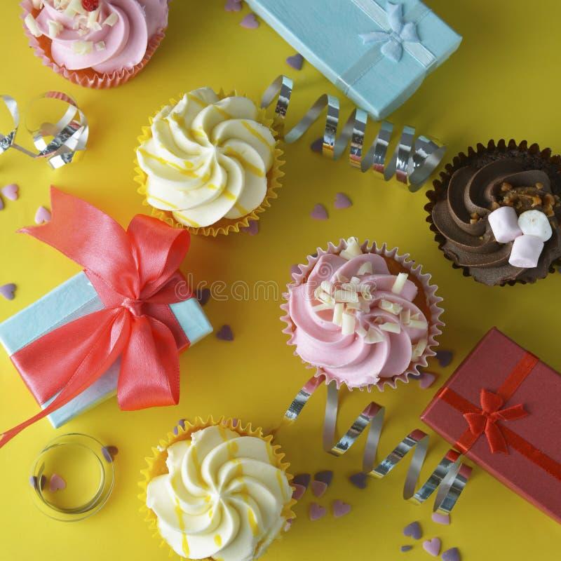 Fondo luminoso e variopinto di compleanno con i bigné, contenitori di regalo, dolci e decorazioni Copi lo spazio Fondo giallo qua immagine stock