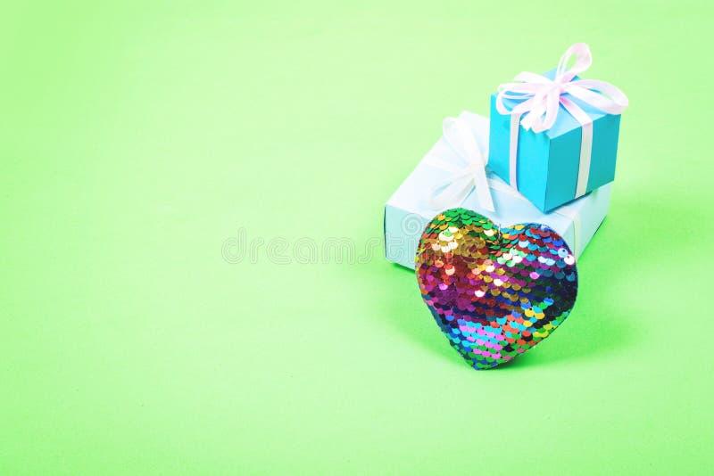Fondo mínimo en colores pastel de día de San Valentín La caja de regalo dos y el AMOR de madera del texto ESTÁ en fondo rosado El foto de archivo