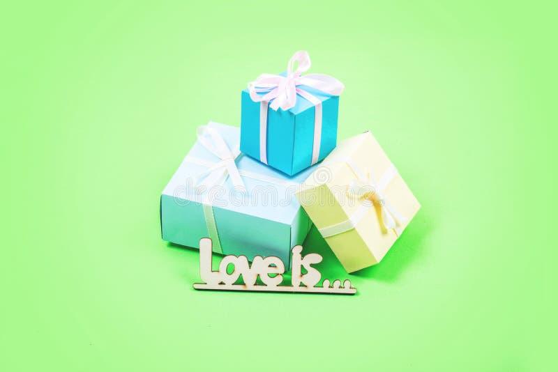 Fondo mínimo en colores pastel de día de San Valentín La caja de regalo tres y el AMOR de madera del texto ESTÁ en fondo rosado E fotos de archivo libres de regalías