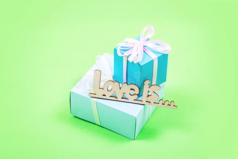 Fondo mínimo en colores pastel de día de San Valentín La caja de regalo tres y el AMOR de madera del texto ESTÁ en fondo rosado E imágenes de archivo libres de regalías