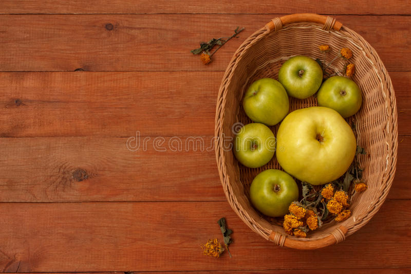 Fondo marrón de madera con una cesta de manzanas verdes imágenes de archivo libres de regalías