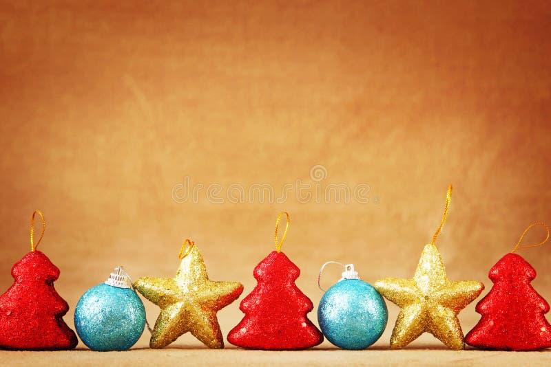 Fondo marrón festivo de la Navidad o del Año Nuevo con una frontera inferior hecha de los juguetes de la Navidad foto de archivo libre de regalías