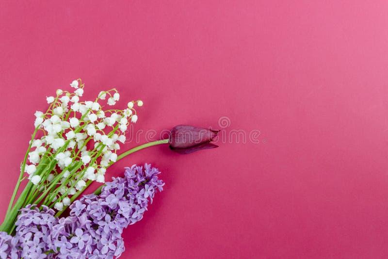 Fondo minimalistic de la primavera con las flores, los tulipanes y los lirios de la lila del valle en la tabla blanca foto de archivo libre de regalías