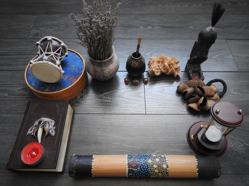 Fondo mistico con un vecchio libro, le candele ed altri attributi Halloween ed il concetto occulto del rituale di magia nera fotografie stock libere da diritti