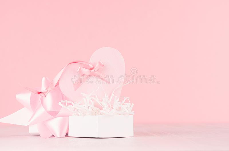 Fondo moderno de los día de San Valentín de la moda - corazón rosado de moda con la cinta y presente en el tablero de madera blan imagen de archivo libre de regalías