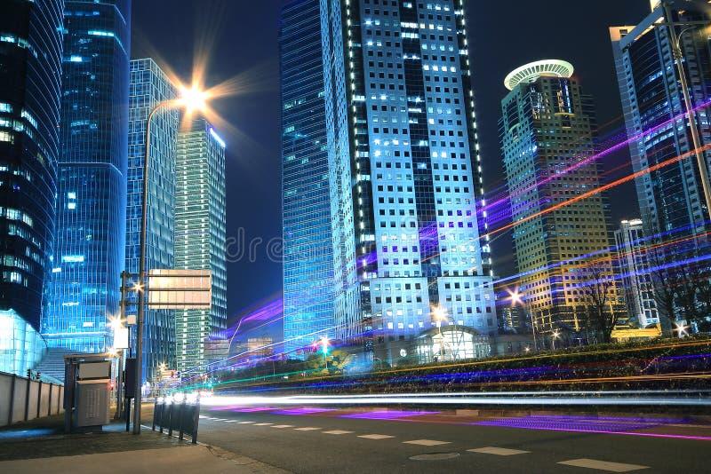 Fondo moderno del edificio de oficinas de la noche del coche con los rastros ligeros fotografía de archivo