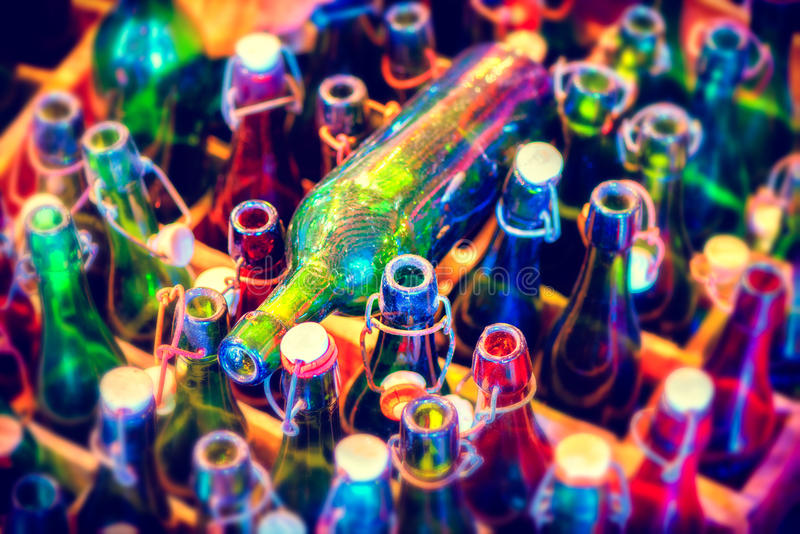 Fondo multicolore con le bottiglie di birra vuote, vista superiore Alimento immagine stock