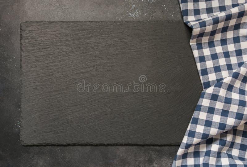 Fondo nero dell'ardesia con l'asciugamano a quadretti blu della cucina Cottura del fondo dell'alimento, di picnic o dell'alimento fotografie stock libere da diritti
