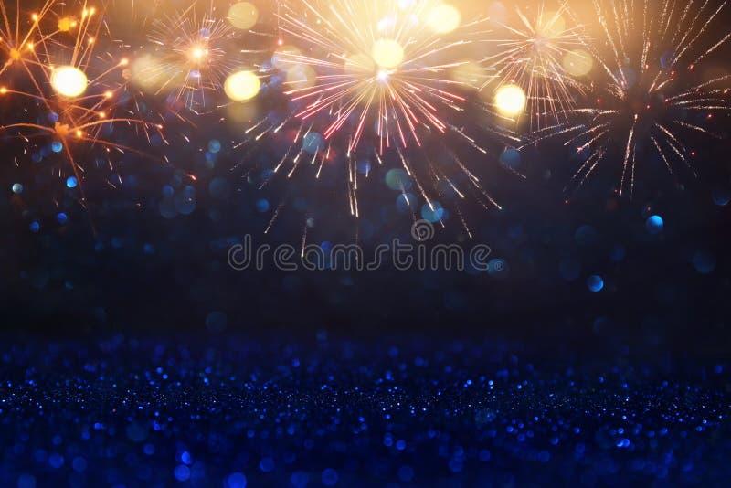 Fondo nero e blu astratto dell'oro, di scintillio con i fuochi d'artificio notte di Natale, quarta del concetto di festa di lugli fotografia stock