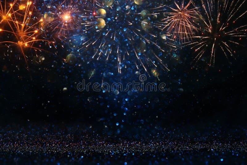 Fondo nero e blu astratto dell'oro, di scintillio con i fuochi d'artificio notte di Natale, quarta del concetto di festa di lugli immagine stock libera da diritti
