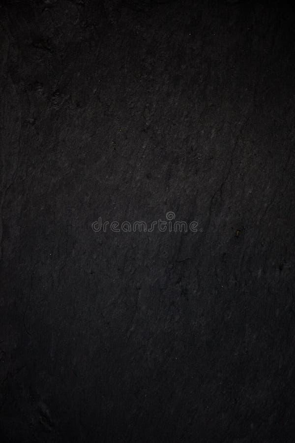 Fondo nero grigio scuro dell'ardesia o struttura di pietra naturale fotografia stock