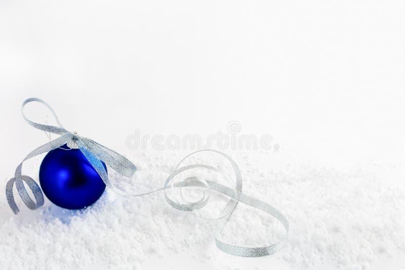 Fondo nevoso de la Navidad con el ornamento azul con la cinta de plata foto de archivo libre de regalías