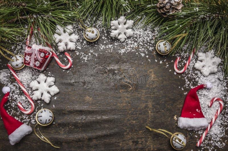 Fondo nevoso de la Navidad rústica de madera con el caramelo, sombrero, decoraciones y ramas verdes del pino y opinión superior d imagenes de archivo