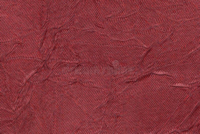 Fondo ondulato rosso scuro da una materia tessile Tessuto con il primo piano di struttura del popolare immagine stock