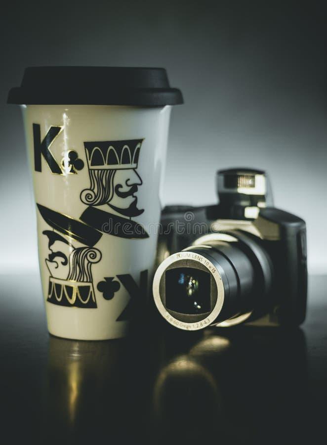Fondo oscuro de la luz de la c?mara digital de la taza de caf? foto de archivo