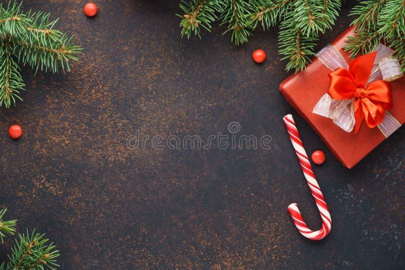 Fondo oscuro de la Navidad con las ramas del abeto, el bastón de caramelo y la caja de regalo foto de archivo