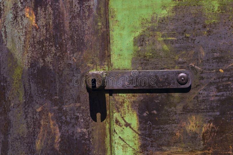 Fondo oxidado de la puerta del metal con viejas capas de pintura verde foto de archivo