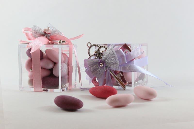 Fondo para el bautismo del bebé con dos favores, rosas y violetas fotos de archivo libres de regalías