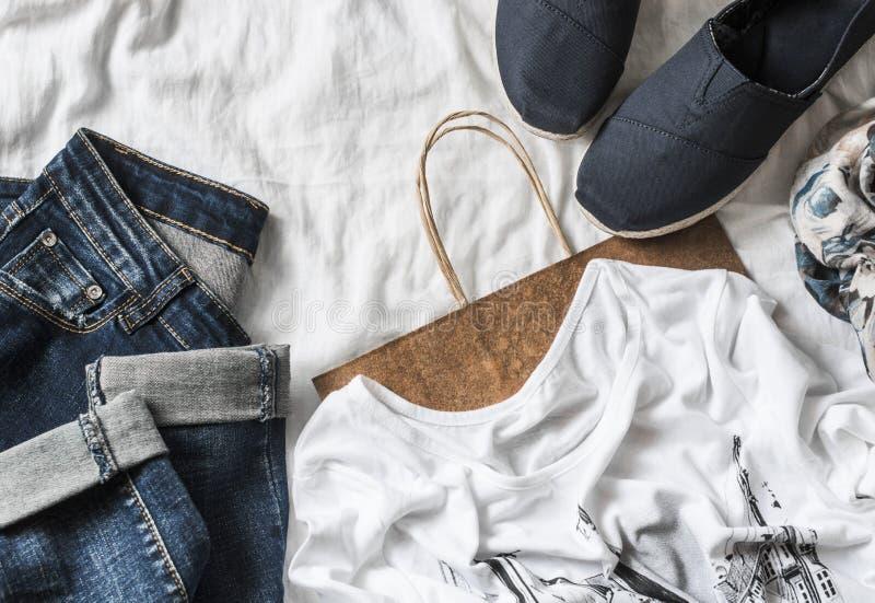 Fondo para mujer de las compras de la ropa Vaqueros, zapatillas de deporte, camiseta, bufanda y una bolsa de papel en un fondo li fotografía de archivo