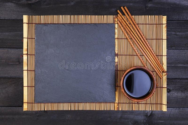 Fondo per i sushi Salsa di bambù di soia e della stuoia sulla tavola di legno nera Vista superiore con lo spazio della copia immagini stock