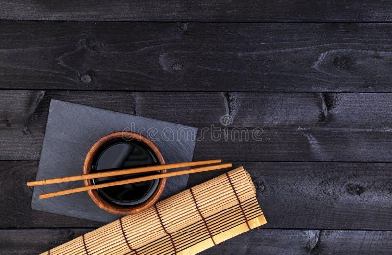 Fondo per i sushi Salsa di bambù di soia e della stuoia sulla tavola di legno nera Vista superiore con lo spazio della copia fotografia stock